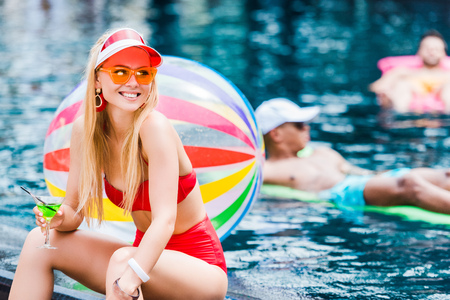 beautiful young woman in swimsuit sitting near swimming pool and drinking cocktail Фото со стока