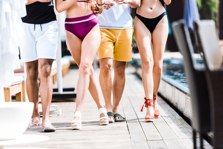cropped image of friends walking near swimming pool