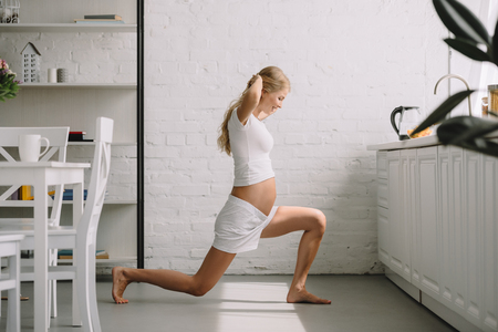 side view of pregnant woman doing fitness exercises at home