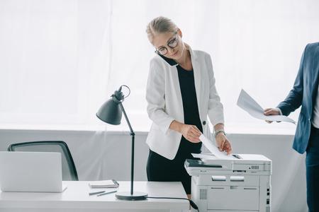 empresaria hablando por teléfono inteligente mientras usa impresora en la oficina con el colega cerca
