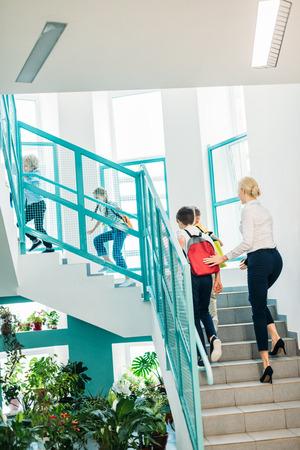 rear view of group of schoolchildren and teacher walking upstairs at school corridor