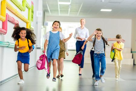 adorable happy schoolchildren running by school corridor together with teacher walking behind