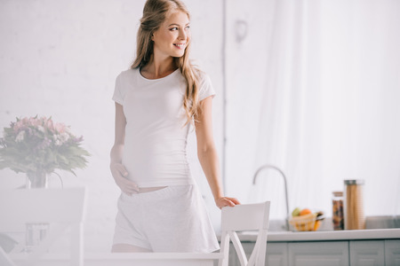 smiling pregnant woman standing at table with bouquet of flowers in vase at home 스톡 콘텐츠