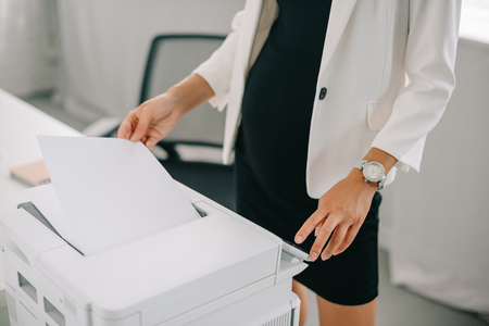 partial view of pregnant businesswoman using printer in office