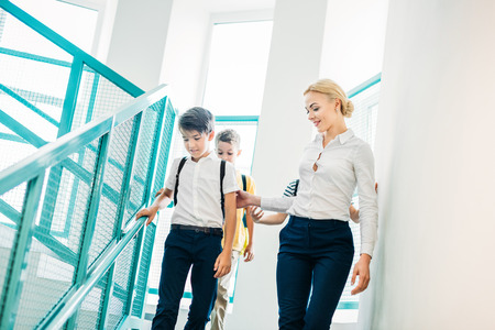 teacher and schoolboys going downstairs together at school corridor Stock Photo