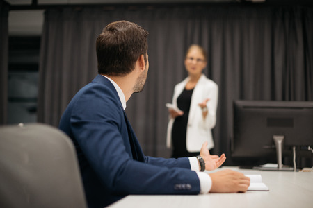 selective focus of businesswoman with smartphone and colleague at workplace discussing project together in office Stock Photo