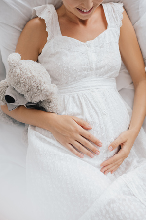 overhead view of smiling pregnant woman in white nightie with teddy bear resting on sofa at home Imagens