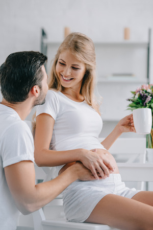 smiling pregnant woman with cup of tea resting on chair and touching belly together with husband near by at home