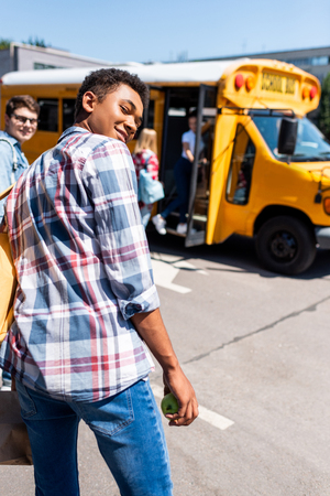 rear view of teen african american schoolboy walking to school bus with his classmates and turning back at camera