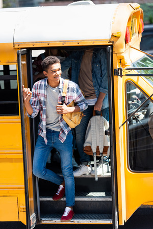 african american happy schoolboy walking out of school bus with classmates