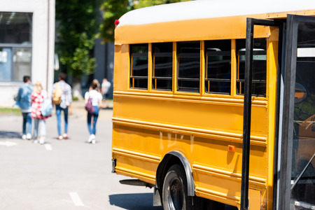 traditional school bus standing on parking with blurred students walking on background