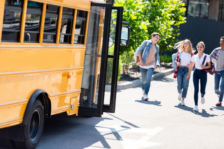 group of teen scholars running to school bus after lessons to get home