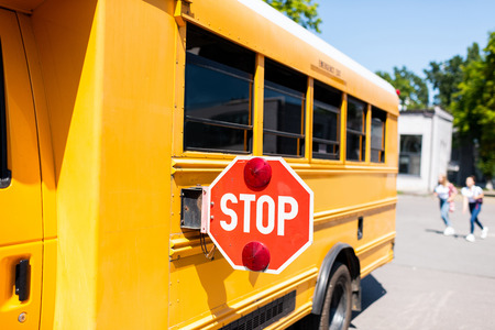 partial view of school bus with stop sign standing on parking with blurred students running on background Stock Photo