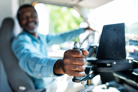 selective view shot of mature african american bus driver pulling lever at bus Stockfoto - 109089788