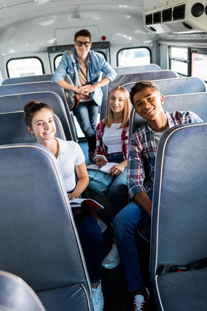 group of smiling teen scholars riding school bus and looking at camera
