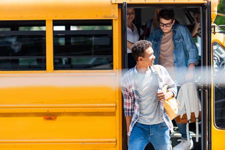 group of teen scholars walking out of school bus 写真素材