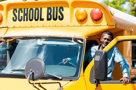 hübscher älterer Schulbusfahrer, der Kamera betrachtet