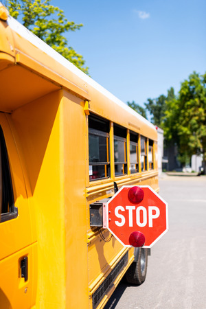 cropped shot of traditional school bus with stop sign Imagens