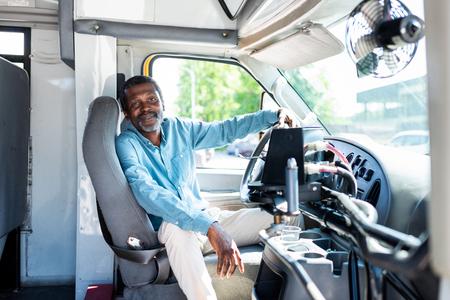 Lachende volwassen Afro-Amerikaanse buschauffeur camera kijken zittend in de bus Stockfoto - 109090182