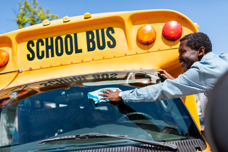happy mature african american bus driver wiping front window of school bus