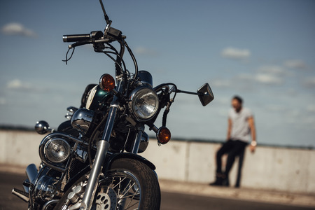 selective focus of classical chopper motorbike and man on background