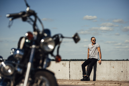 selective focus of young biker with classic motorcycle on foreground