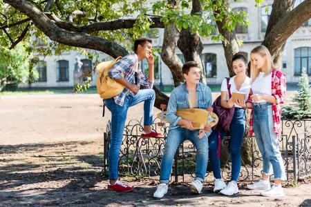 group of teenagers sitting at school garden together 版權商用圖片