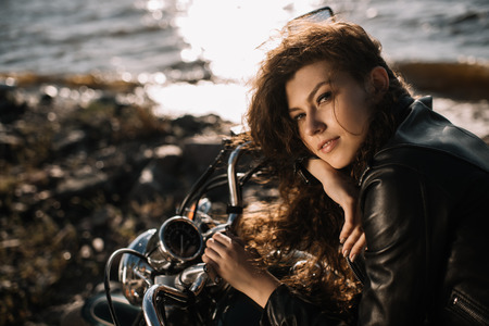 beautiful girl sitting on classical motorcycle