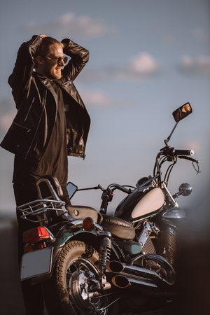 frustrated handsome biker with classical motorcycle on road Stock Photo