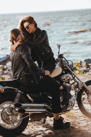 couple of bikers hugging on classical motorcycle on seashore