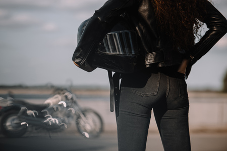 cropped view of woman holding moto helmet, motorbike standing on background