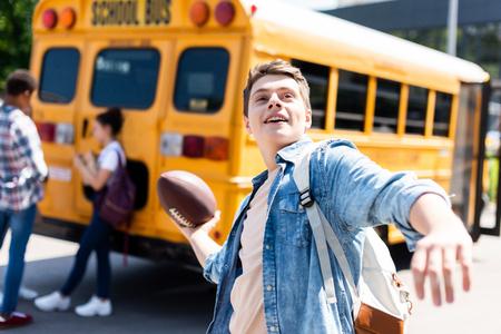 smiling teen schoolboy throwing american football ball in front of school bus 写真素材 - 111763449