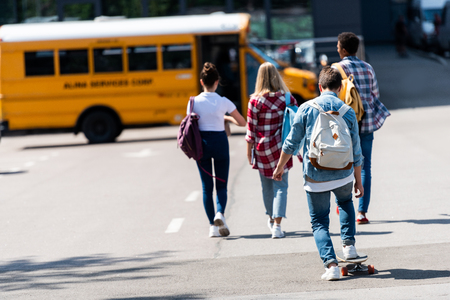 rear view of group of teen scholars walking to school bus by parking