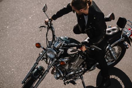 biker sitting on vintage chopper motorcycle on asphalt road