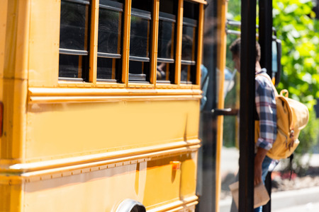 african american schoolboy walking into school bus Stok Fotoğraf