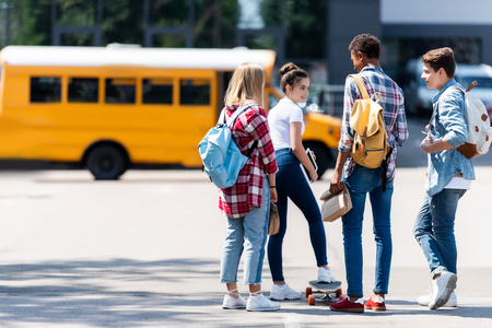 group of teen scholars spending time together on parking in front of school bus