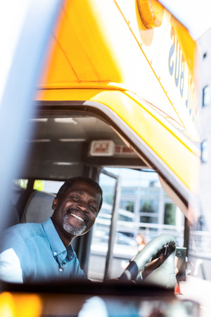 happy mature african american bus driver looking at camera Фото со стока