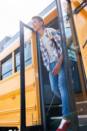 Vista inferior del colegial afroamericano adolescente feliz saliendo del autobús escolar