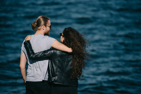 rear view of young couple hugging near the sea