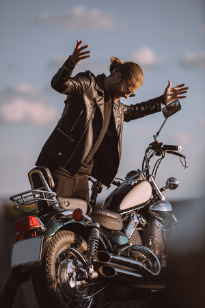 angry handsome man with broken motorcycle on road