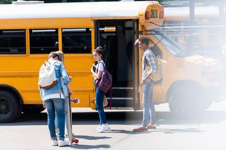 group of teen scholars standing near school bus