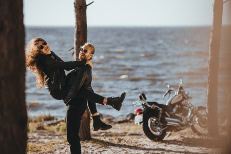 boyfriend having fun and holding his girlfriend on arms on seashore with motorcycle near