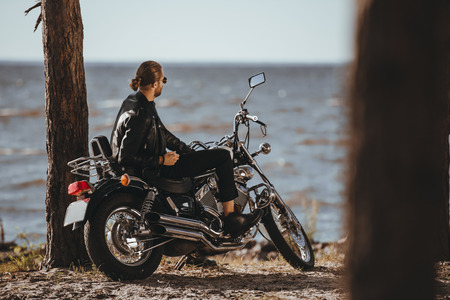 biker in leather jacket sitting on classical motorbike near the sea 스톡 콘텐츠