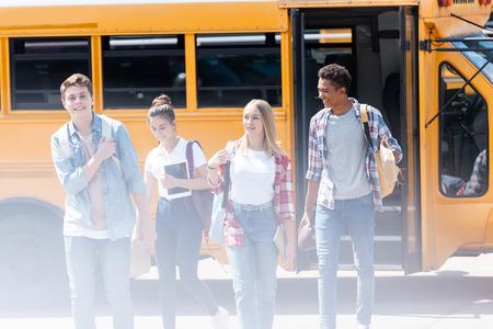 group of teen scholars walking together in front of school bus
