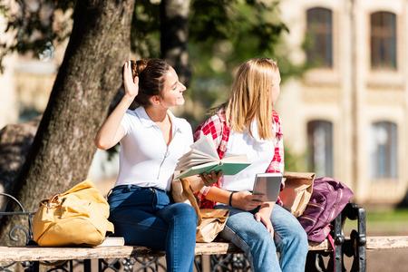 teen schoolgirls sitting on bench and reading homework together 写真素材