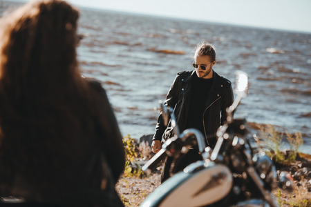 selective focus of woman sitting on motorbike and looking at boyfriend walking on seashore