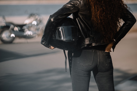 cropped view of woman holding helmet, motorcycle standing on background