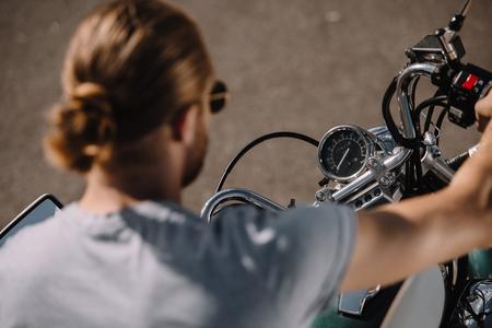 biker sitting on vintage classic motorbike, selective focus