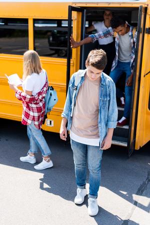 sad teenager schoolboy standing in front of school bus with classmates