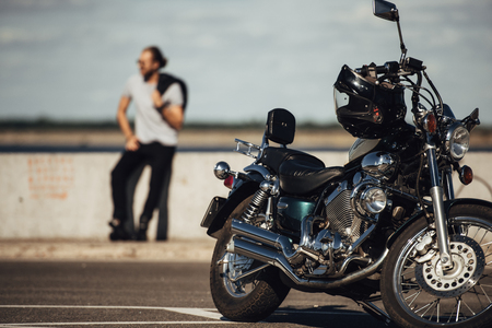 selective focus of chopper motorcycle and biker on background Imagens